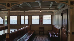 the upper deck of the steam ferry showing original rows of wooden seating