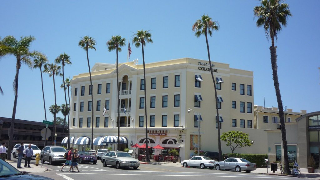 photo shows the front of the Grand Colonial Hotel and palm trees surrounding it