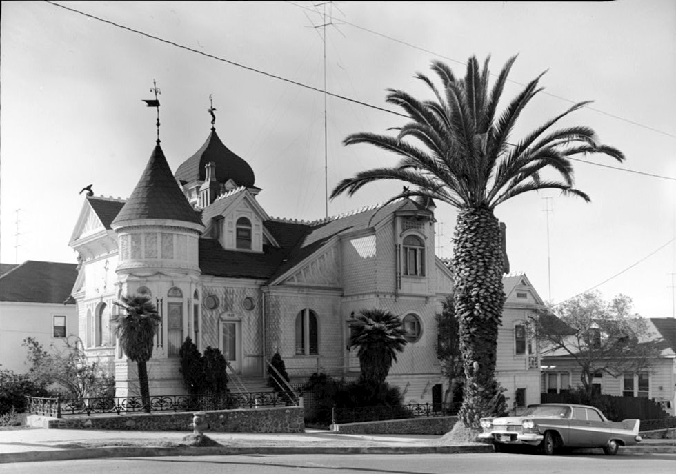 photo is black and white and shows the front entrance of the villa montezuma. it looks as if it is made from stucco with a large palm tree out front