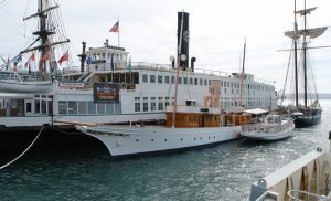 Photo shows the Berkeley sitting in the water, with its its large black tower on top and sides full of passenger windows. On the side of the vessel, the word 'Berkeley' is painted.