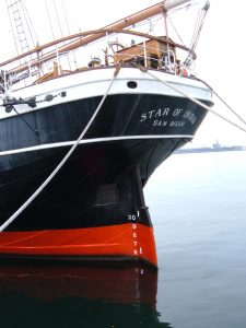 Photo shows the Star of India's stern. She is painted bloack with a red stripe, and the words 'Star of India, San Diego' are painted on top.
