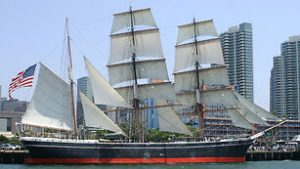 Photo shows the entire Star of India, with three masts and white sails. The ship is painted black with a fire engine red stripe down the entire side.